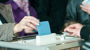 main qui met une enveloppe dans une urne de vote