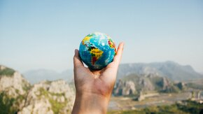une main qui tient un globe vers le ciel
