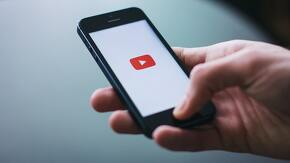 Main tenant un portable avec logo Youtube en fond d'écran