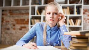 Jeune femme blonde assise à une table avec des livres