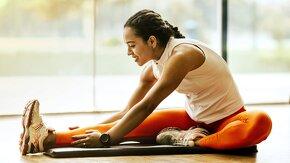 Jeune femme fait du stretching sur un tapis de sport