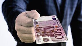 Main d'un homme qui tend un billet de 500 euros