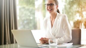 Jeune femme blonde souriante devant un ordinateur portable
