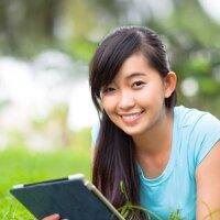 Jeune fille avec tablette dans l'herbe