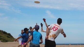 Amis jouant au frisbee sur la plage