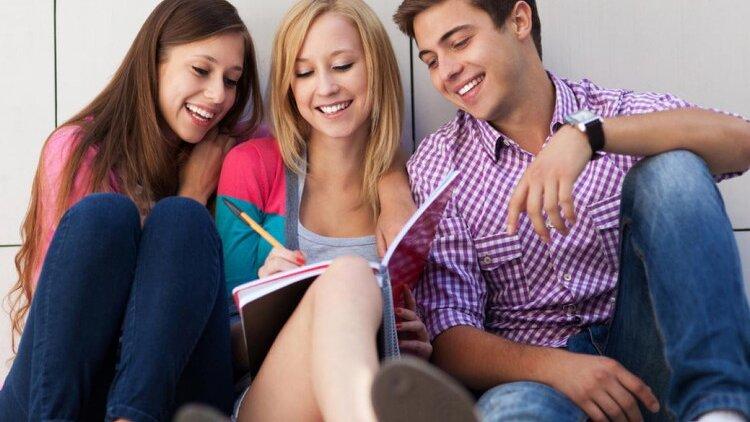 Des jeunes écrivent sur un cahier.