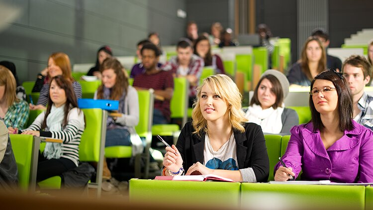 Étudiantes suivent un cours en amphithéâtre.